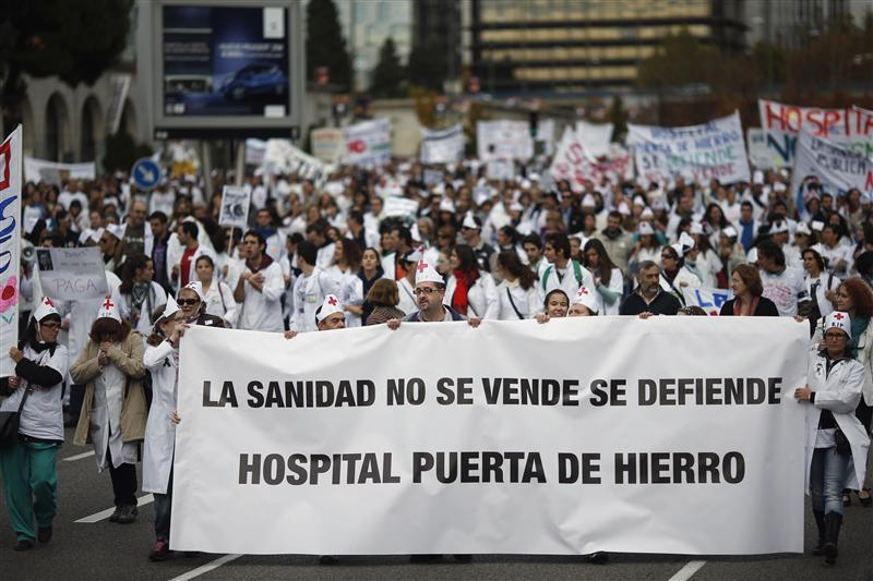 Demonstrators march behind a banner that reads Healthcare is not for sale, we have to defend it. Puerta de Hierro hospital during a protest in Madrid